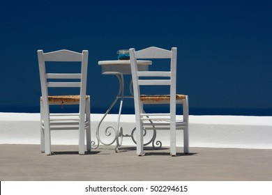 White chairs on a white roof (Greece)