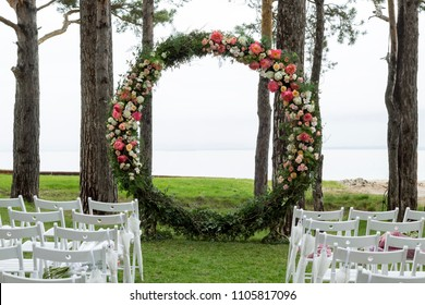 White chairs, round wedding arch with flowers in forest near sea. Close-up, copy space, toned. Invitation, love concept
