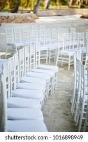 white chairs set up on the beach for wedding