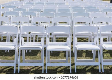 White Chairs Set Up for Wedding spanning image
