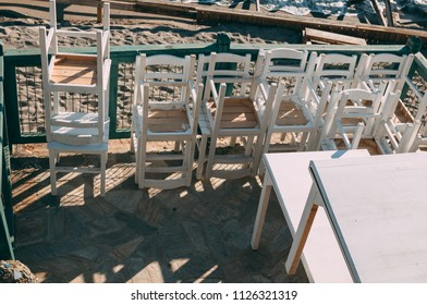 A lot of white chairs stacked on top of each other at sunset stand on the embankment near the sea