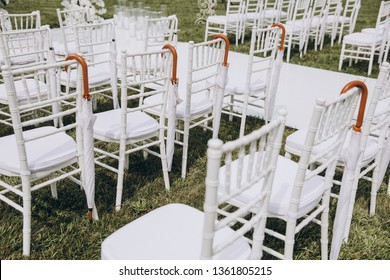 white chairs stand on green grass in the area of the wedding ceremony, white umbrellas are hanging on the chairs
