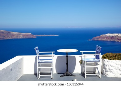 white chairs and tables beside Aegean sea, Santorini, Greece