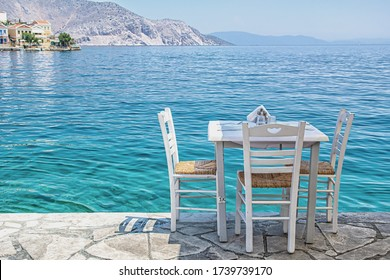 White chairs with tables in typical Greek tavern near the sea in Symi town
