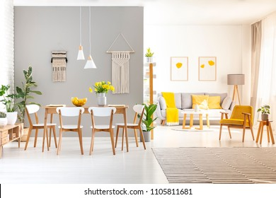 White chairs at wooden dining table in bright apartment interior with yellow armchair. Real photo