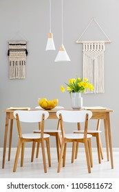 White chairs at wooden table with yellow flowers in grey dining room interior with lamps. Real photo