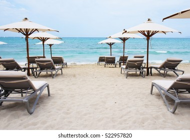 White chaise longue and umbrellas on the empty sandy beach at azure sea