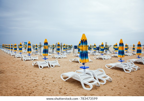 white chaise lounges and colored umbrellas in perspective on the beach. The sea, the sand.