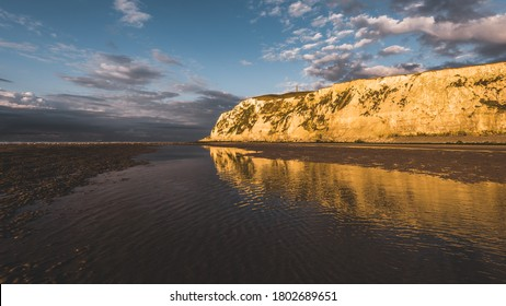 White chalk cliff of Cap Blanc Nez on the coast of France at the Straight of Dover (Pas de Calais) during sunset, the WWI Dover Patrol Memorial in the background. Dramatic sky. Travel destinations