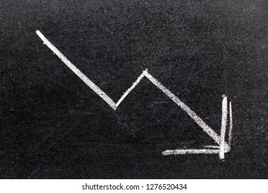White chalk hand drawing in arrow down shape on black board background (Concept of stock decline, down trend of business, economy)