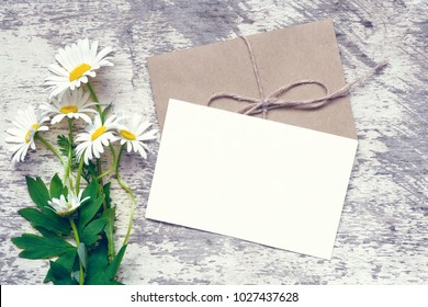 white chamomile flowers and blank white greeting card with envelope over rustic wooden background. mock up. flat lay. vintage toning
