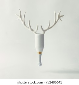 White Champagne bottle with reindeer antlers on bright background. New year party concept.