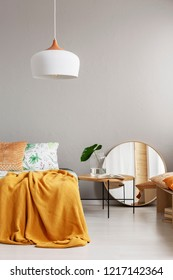White chandelier above comfortable bed with yellow blanket in stylish bedroom interior, real photo with copy space on the empty grey wall