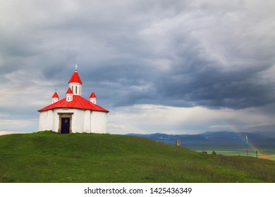 White chapel against dark blue sky with a rainbow