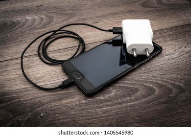 The white charger and black mobile phone are placed on a wooden table.