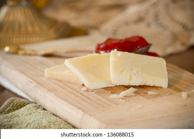 White cheddar cheese slices on cutting board with strawberry jam in the background