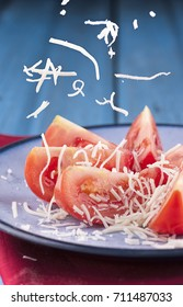 White cheese falling on tomato slices.