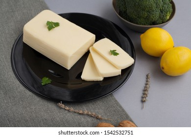 The white cheese lies in a large lump on a black plate decorated with parsley, next to lemons, walnuts and Brussels sprouts, the whole composition on a grey tablecloth. The concept of cheese products.