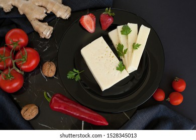 White cheese on a black plate, decorated with strawberries, red pepper, dill, cherry tomatoes and walnuts, on a dark background. The concept of cheese products.