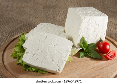 White cheese with some garnitures such as lettuce, a slice of cherry tomato and bassil on a wooden plate with sackcloth table sheet