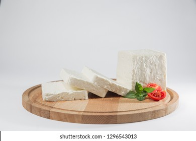 White cheese with some garnitures such as lettuce, cherry tomato slice and basil on a wooden plate, white background