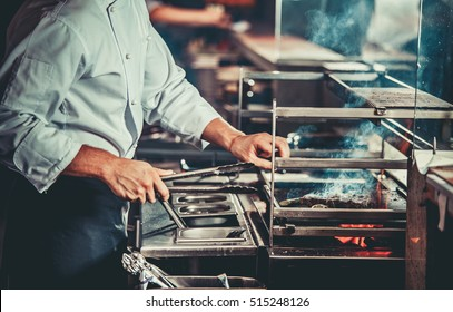 White chef in apron standing near the brazier whith coals, only hands. Man cooking beef steak in the interior of modern professional kitchen