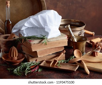 White chef's hat and old cookbooks. Kitchen utensils with spices and rosemary on a kitchen table.