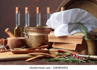 White chef's hat and old cookbooks. Kitchen utensils with bottles of olive oil, spices and rosemary on a kitchen table.