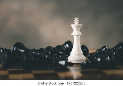 White Chess King among lying down black pawns on chessboard, chess board game for ideas and competition and strategy, Planning and Decision concept.
