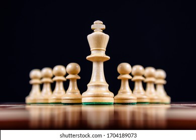 white chess king with pawns on a black background