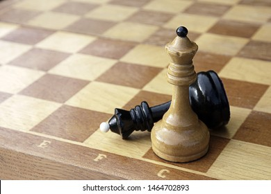 White chess king put checkmate to black king. Two chess pieces on wooden chess board. Black king figure lying defeated next to white winner.
