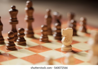 White chess knight alone facing black pieces.