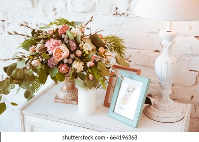 White chest of drawers on a white brick wall background with flower arrangement, lamp and decorative elements