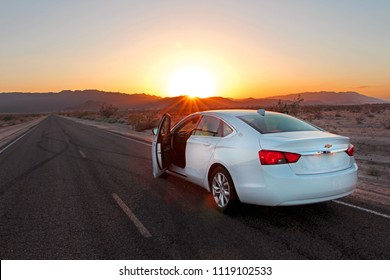 White Chevrolet Impala with front doors opened parked on the empty road near Death Valley National park during beautiful sunset, California - June 1, 2018.
