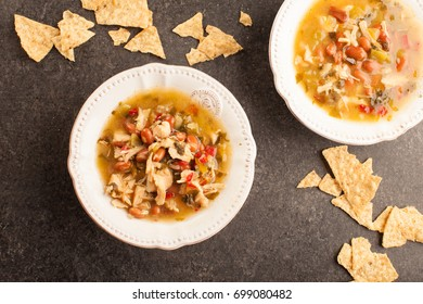 White chicken chili with red peppers, chicken, and beans in white bowl with corn tortilla chips horizontal shot