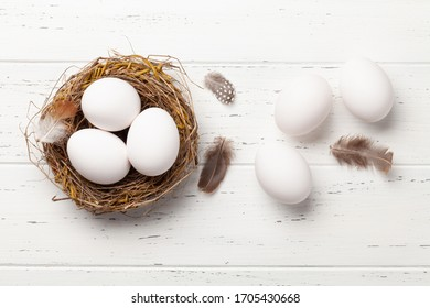 White chicken eggs in nest on wooden background. Easter greeting card. Top view with copy space. Flat lay