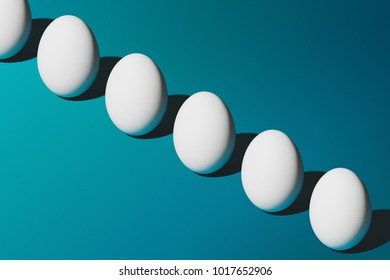 White Chicken eggs on blue background, Easter pattern top view. Minimal design with space for text, horizontal image.