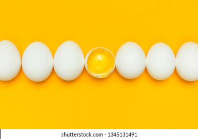 White chicken eggs and one broken egg with yolk on yellow background top view flat lay copy space. Creative food minimalistic background, Easter. Natural healthy food and organic farming concept.