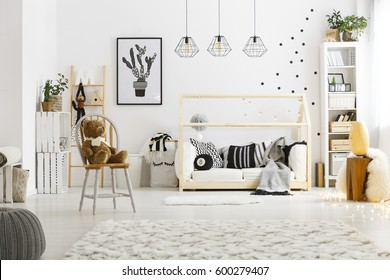 White child bedroom with carpet, pouf, chair, bed and bookcase