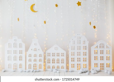 White children room with decorative wooden houses. White wooden decorative houses on wall background. Toy houses in Christmas decor. Interior of the children's room. Paper garland in the form of stars