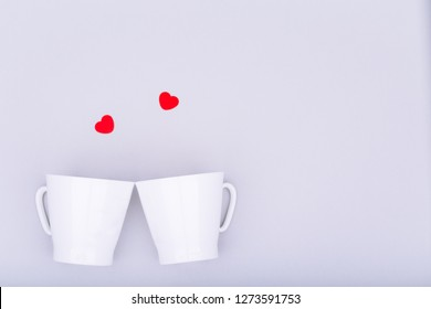 White china mug with  glitter heart confetti. Valentine day concept. Trendy minimalistic flat lay design background. Horizontal