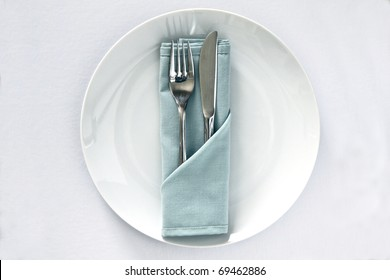 White china plate with serivette and knife and fork isolated on a white background