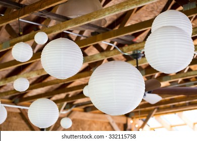 White Chinese paper lanterns hung in a barn as diy wedding reception decor.