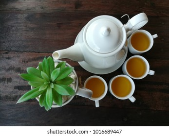 White Chinese teapot and cups on wooden table background.
