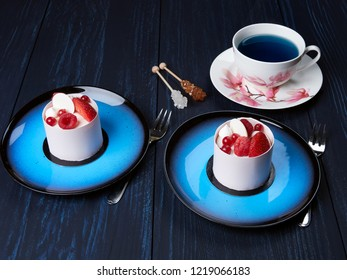 White chockolate cake with strawberies, raspberries and redcurrants served on a blue plate, with a cup of blue tea