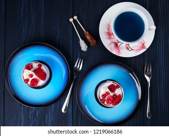 White chockolate cake with strawberies, raspberries and redcurrants served on a blue plate, with a cup of blue tea, top view