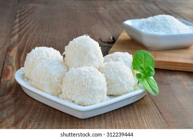 White chocolate candy coconut truffles on heart shaped plate over wooden table.