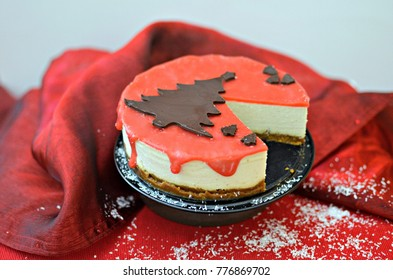 White chocolate cheesecake with strawberry sauce, sliced, red background.