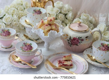 White chocolate and raspberry fudge with vintage pink teacups, teapots, gold cutlery flatware and roses - high tea party