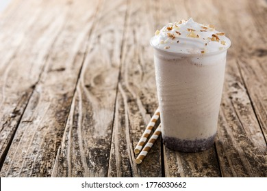White chocolate, vanilla and nuts iced milkshake on rustic wooden table.Copy space